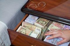 Main sur l'argent dans la table de chevet Photos stock