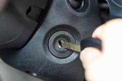 Main sur la clé insérée dans le commutateur de la voiture photographie stock