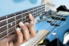 Main sur la guitare basse Photographie stock libre de droits