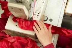 Main sur la machine à coudre piquant le ruban rouge et le tissu hérissé Photo stock