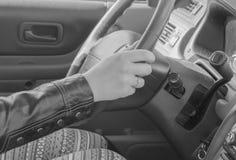Main sur la roue d'une voiture un jour ensoleillé, noire et blanche Images stock