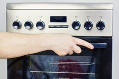 Main sur le cuiseur électrique photo libre de droits