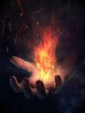 Main sur le feu Image stock