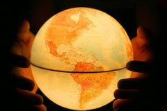 Main sur le globe léger Photo stock