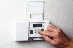 Main sur le thermostat Photo stock