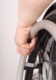 Main sur un fauteuil roulant Photos stock