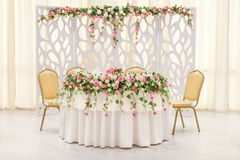 The main table of the newlyweds, decorated with a floral composition and an arch in pastel colors Stock Photos