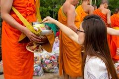 Main tandis que les offres mises de nourriture dans l'aumône de moine bouddhiste roulent f photos libres de droits