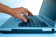 Main tapant sur un ordinateur portatif Images libres de droits