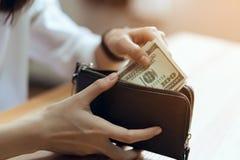 Main tenant 100 billets d'un dollar dans le portefeuille Le concept de la dépense par l'argent liquide Photos libres de droits