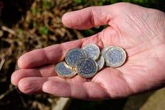 Main tenant de nouvelles pièces de monnaie de livre image stock