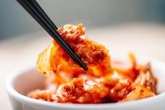 Main tenant des baguettes pour manger du chou de kimchi image stock