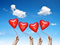 Main tenant des ballons d'un coeur de rouge Photos libres de droits