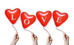 Main tenant des ballons d'un coeur de rouge Photo libre de droits