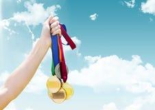 Main tenant des médailles devant le ciel Image libre de droits