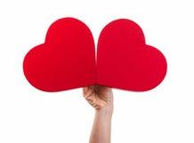 Main tenant deux coeurs rouges Photo libre de droits