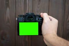 Main tenant et prenant le tir avec la caméra mirrorless d'affichage vert sur la table en bois photo libre de droits
