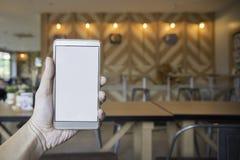 Main tenant l'écran vide du téléphone intelligent avec la séance brouillée dessus Images libres de droits