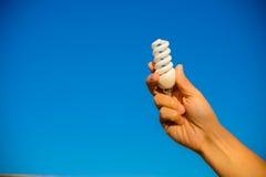 Main tenant l'ampoule électrique économiseuse d'énergie sur le bleu Images libres de droits