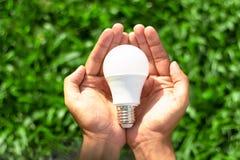 Main tenant l'ampoule de LED avec l'éclairage sur le fond vert de nature photographie stock