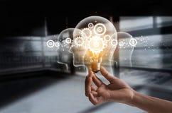 Main tenant l'ampoule et la dent à l'intérieur Idée et imagination photos stock