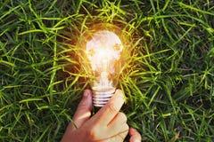 main tenant l'ampoule sur l'herbe énergie de puissance de concept d'eco en Na photos libres de droits