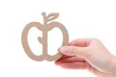 Main tenant l'imitation de la pomme en bois Photographie stock libre de droits