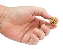 Main tenant la boule de bonbons au chocolat avec le sésame Image stock