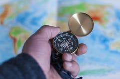 Main tenant la boussole devant la carte du monde Photo stock