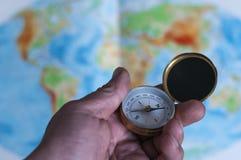 Main tenant la boussole devant la carte du monde Images stock