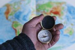 Main tenant la boussole devant la carte du monde Image stock