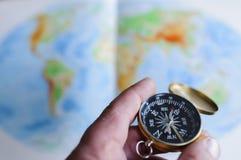 Main tenant la boussole devant la carte du monde Photographie stock