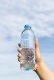 Main tenant la bouteille d'eau sur le nuage et le ciel Photo stock