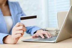 Main tenant la carte de crédit dactylographiant sur le clavier de l'ordinateur portable pour le concept de achat en ligne de comm image libre de droits