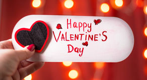 Main tenant la carte heureuse de jour de valentines Photo stock