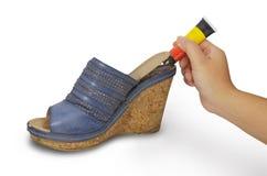 Main tenant la colle réparant la chaussure Photographie stock