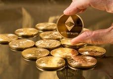 Main tenant la pièce de monnaie d'éther au-dessus des bitcoins photographie stock libre de droits