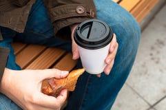 Main tenant la tasse de café avec le croissant Photographie stock libre de droits