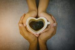 Main tenant la tasse de forme de coeur de café Image libre de droits