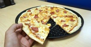 main tenant la tranche de pizza Photo libre de droits