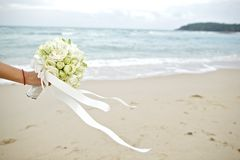 Main tenant le bouquet de mariage avec le fond de plage images libres de droits