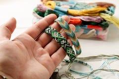 Main tenant le bracelet tissé différent d'amitié, plan rapproché tiré images libres de droits