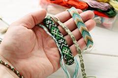 Main tenant le bracelet tissé différent d'amitié, plan rapproché tiré image stock