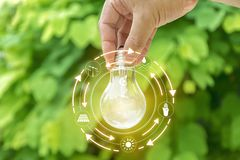 Main tenant le bulbt léger Concept d'écologie photographie stock