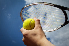 Main tenant le ciel d'agaist de balle de tennis et de raquette Photographie stock libre de droits