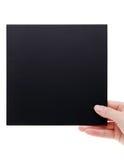 Main tenant le conseil noir Image stock