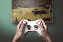 Main tenant le contrôleur de console de jeu jouant le jeu photographie stock libre de droits