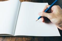 Main tenant le crayon et le papier Photo stock