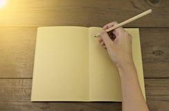 Main tenant le crayon sur le carnet Photos libres de droits