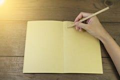Main tenant le crayon sur le carnet Photo libre de droits